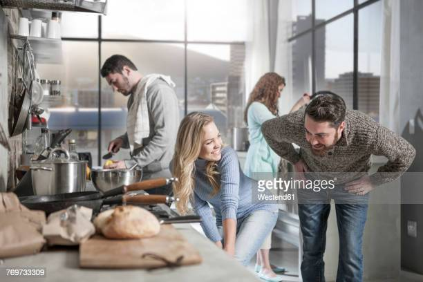 friends preparing meal in kitchen - heterosexual couple stock pictures, royalty-free photos & images