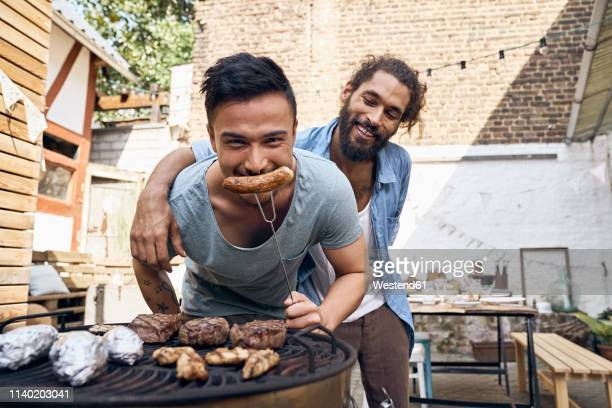 friends preparing meat for a barbecue in the backyard - only men stock-fotos und bilder