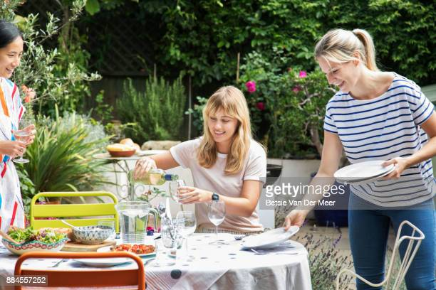 Friends preparing table for garden party.