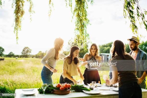 friends preparing table of food outdoors - farm to table stock photos and pictures