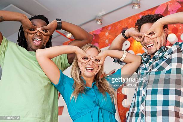 Friends pretending to wear glasses at a bar