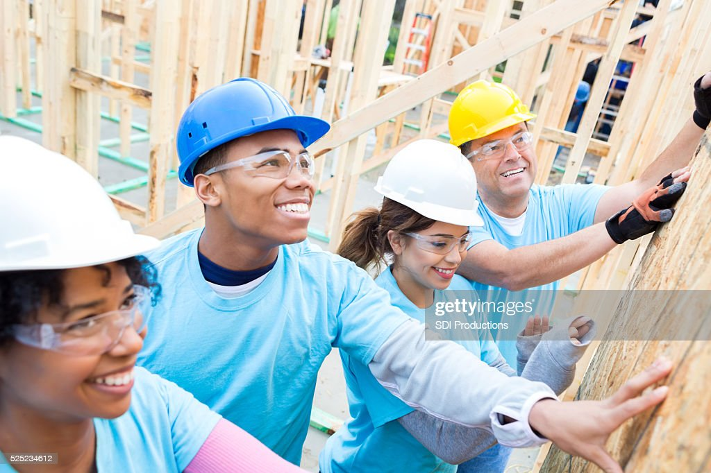 Friends proudly put up wall in charity home : Stock Photo