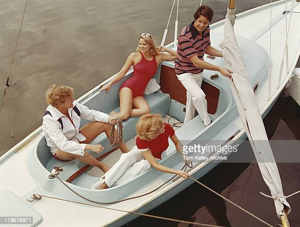 Friends pulling rope in sailing boat, smiling