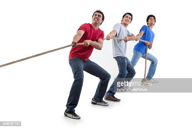 Friends pulling rope together over white background