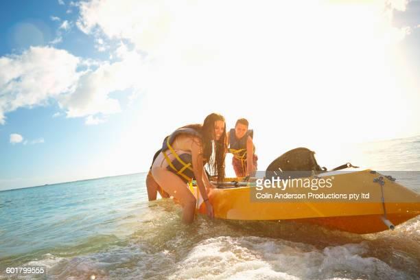 Friends pushing canoe on beach