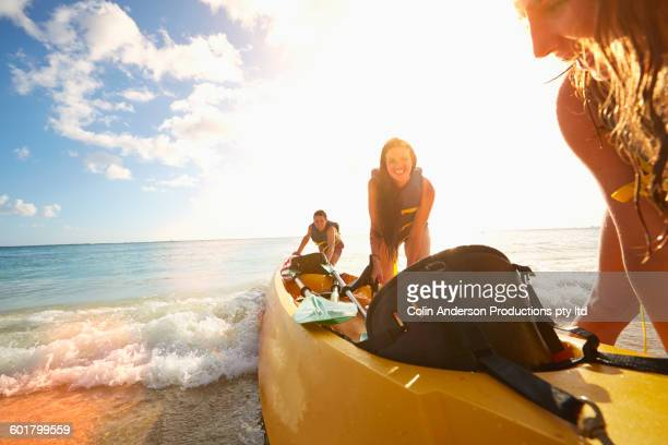 Friends pushing canoe on beach