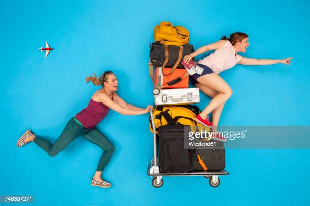 friends pushing luggage trolley, hurrying for departure - オフビート ストックフォトと画像