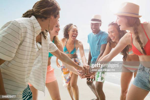 Friends putting hands together on beach