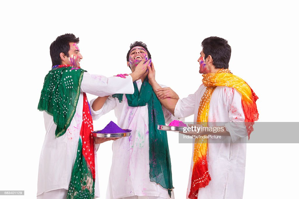 Friends putting holi colours on each other : Stock Photo