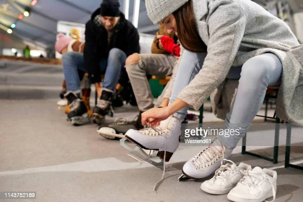 friends putting on ice skates at an ice rink - ice skate stock pictures, royalty-free photos & images