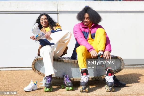 friends putting on rollerskates - skating stock pictures, royalty-free photos & images