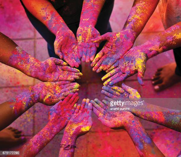 Friends putting their hands together, smeared with multicolors during the Hindu festival of Holi.