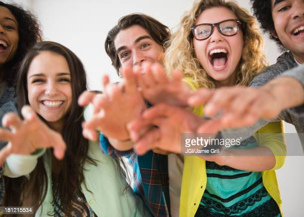 friends reaching out together - hysteria stock pictures, royalty-free photos & images