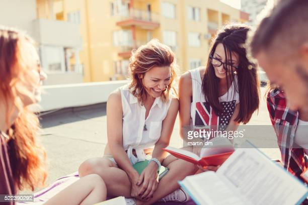 Friends reading books on the rooftop