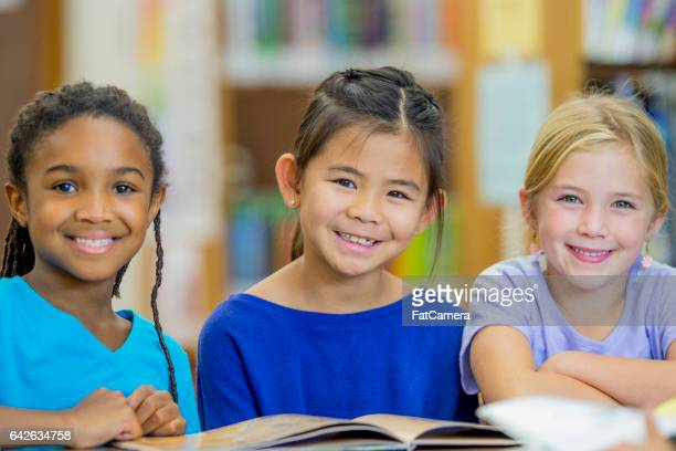 friends reading together in the library - small group of people stock pictures, royalty-free photos & images