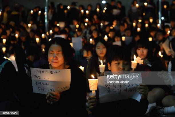 Friends relatives and neighbors gather for a candlelight vigil at Danwon High School on April 18 2014 in Ansan South Korea The woman's sign reads...