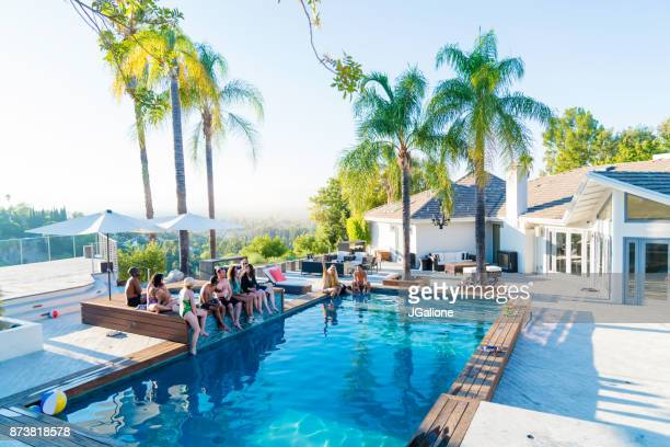 friends relaxing at a luxury pool together - pool party stock pictures, royalty-free photos & images