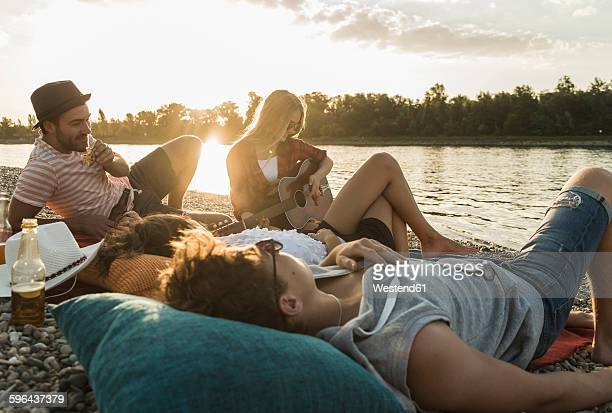 friends relaxing at the riverside at sunset - wochenendaktivität stock-fotos und bilder