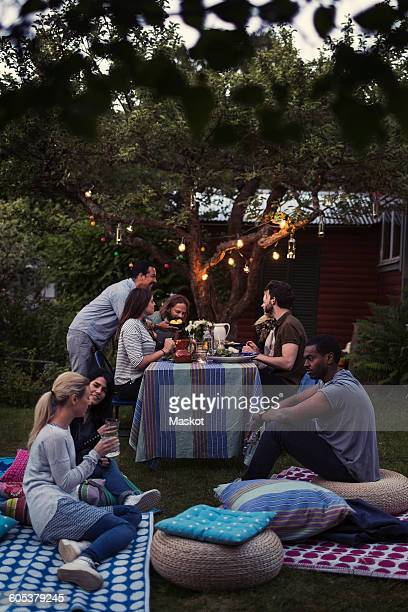 Friends relaxing at yard during dinner party
