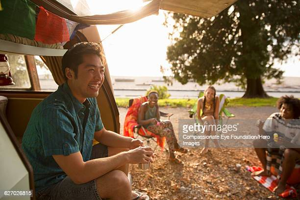 """friends relaxing by camper van - """"compassionate eye"""" stock pictures, royalty-free photos & images"""