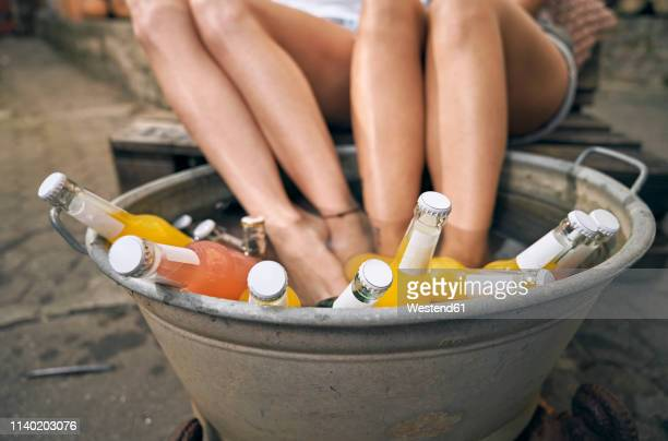 friends relaxing in a backyard in summer, young women cooling their feet in a tub with drinks - kaltes getränk stock-fotos und bilder