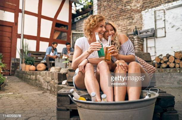 friends relaxing in a backyard in summer, young women cooling their feet in a tub with drinks - cleaning after party bildbanksfoton och bilder