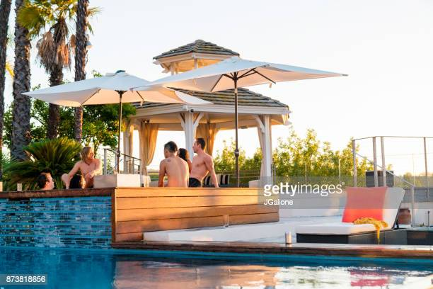 Friends relaxing in a luxury hot tub outdoors at sunset