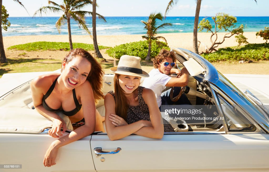 Friends relaxing in convertible on beach : Foto stock