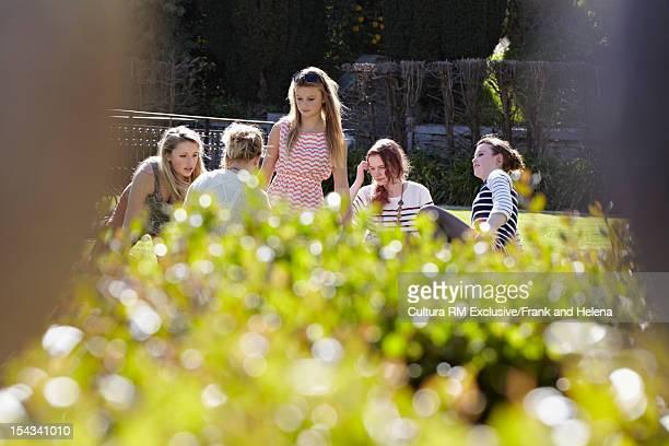 Friends relaxing in garden outdoors