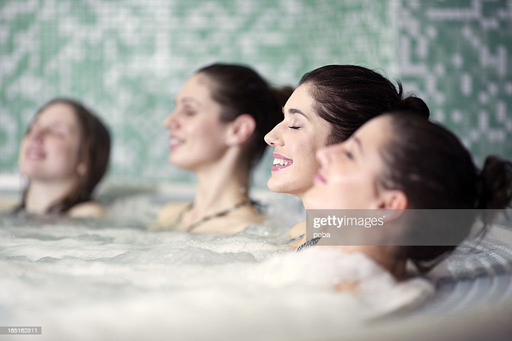 friends relaxing in hot tub at health spa : Stock Photo