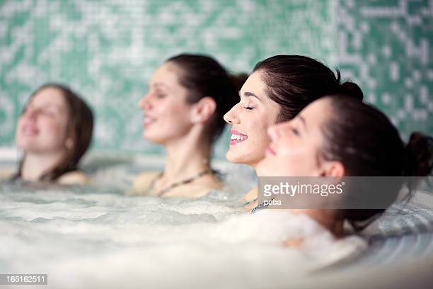 friends relaxing in hot tub at health spa - hot tub stock photos and pictures