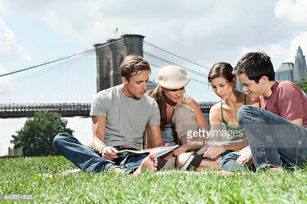 Friends relaxing in park in front of Brooklyn Bridge, New York City, USA