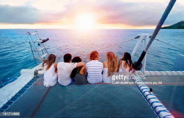 friends relaxing on boat in ocean - catamaran stock photos and pictures