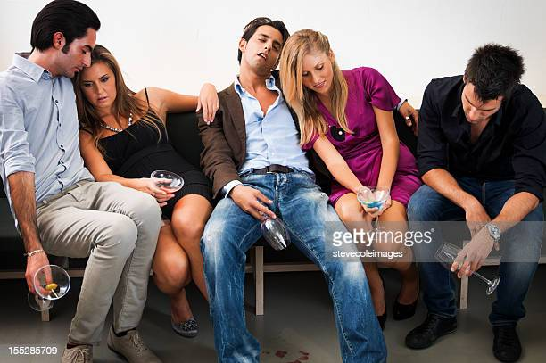 Friends Relaxing On Couch After Party