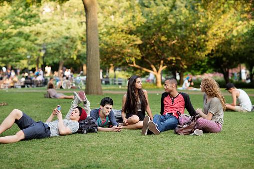 Friends relaxing on field in campus - gettyimageskorea