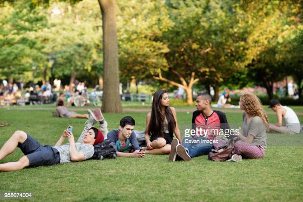 friends relaxing on field in campus - gras stock pictures, royalty-free photos & images