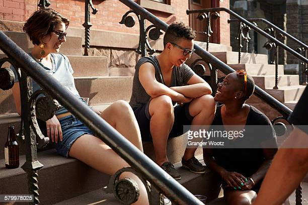 friends relaxing on front stoop - ポーチ ストックフォトと画像