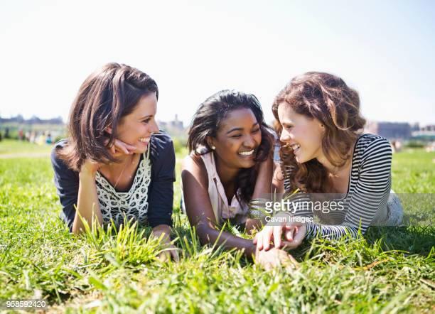 friends relaxing on grassy field against sky - op de buik liggen stockfoto's en -beelden