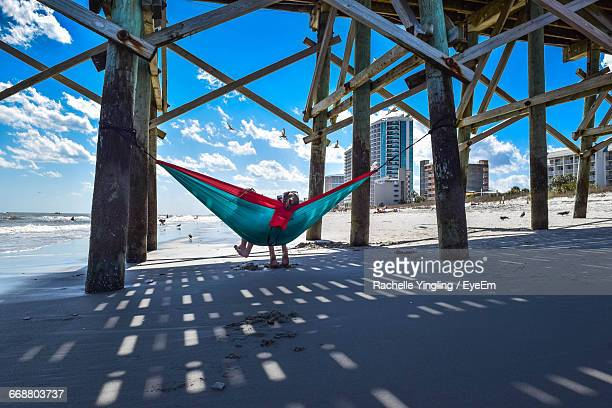 friends relaxing on hammock below pier at beach - file:myrtle_beach,_south_carolina.jpg stock pictures, royalty-free photos & images