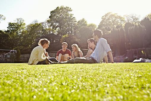 Friends relaxing on manicured lawn - gettyimageskorea