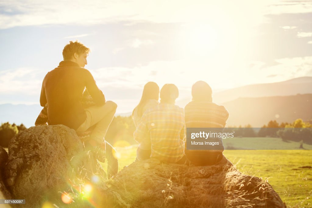 Friends relaxing on rock at field : Stock Photo