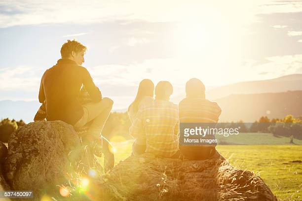 friends relaxing on rock at field - gegenlicht stock-fotos und bilder