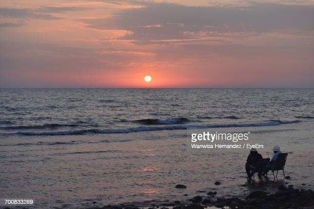 Friends Relaxing On Sea Shore At Beach Against Sky During Sunset