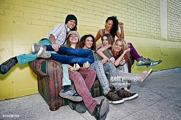 Friends relaxing on sofa on city street