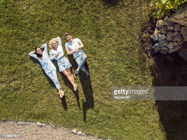 friends relaxing on the grass in summer - lying down foto e immagini stock