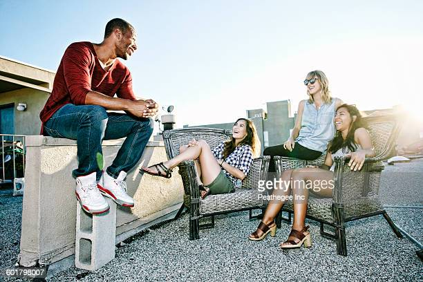 Friends relaxing on urban rooftop