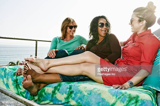 friends relaxing together at waterfront - creole ethnicity stock pictures, royalty-free photos & images