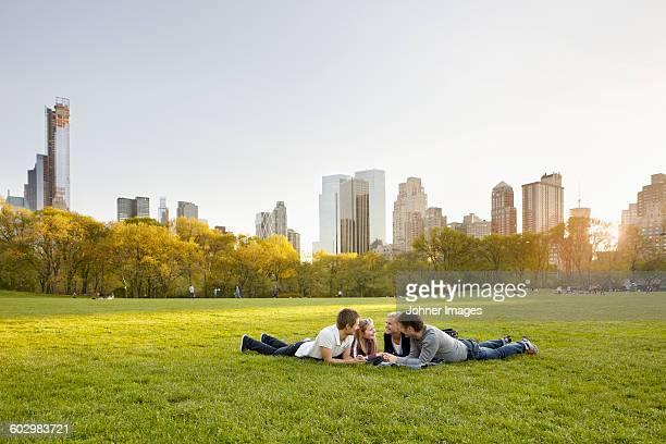 friends relaxing together in park - acostado boca abajo fotografías e imágenes de stock