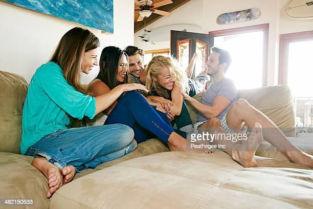 friends relaxing together on sofa - kitzeln stock-fotos und bilder