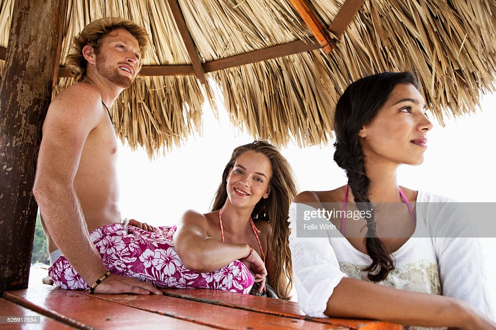 Friends relaxing under sunshade : Stock Photo